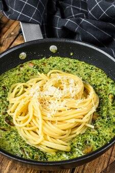 鍋にペストソースと新鮮なほうれん草とパルメザンチーズを添えたパスタスパゲッティ。木製の背景。上面図。