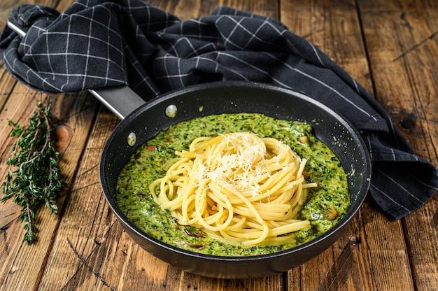 Паста спагетти с соусом песто и свежим шпинатом и пармезаном на сковороде