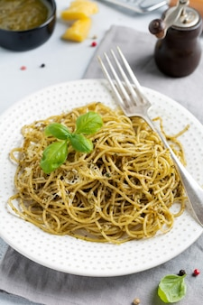Паста спагетти с соусом песто, базиликом и сыром пармезан на белой керамической тарелке и сером фоне бетона или камня. традиционное итальянское блюдо. выборочный фокус. вид сверху.