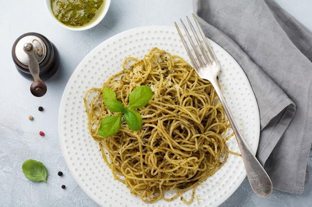 흰색 세라믹 접시와 회색 콘크리트 또는 돌 배경에 페스토 소스, 바질, 파르 메산 치즈와 파스타 스파게티. 전통적인 이탈리아 요리.