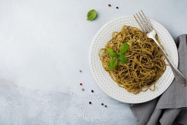 白いセラミックプレートと灰色のコンクリートまたは石の表面にペストソース、バジル、パルメザンチーズを添えたパスタスパゲッティ。伝統的なイタリア料理。セレクティブフォーカス。上面図。