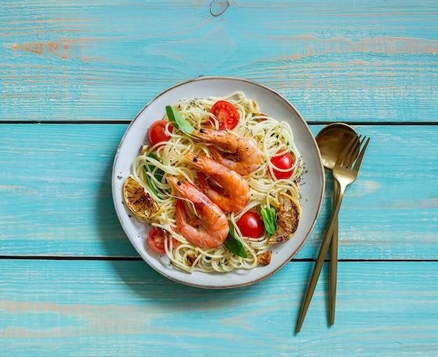 エビ、トマト、ニンニク、ほうれん草、レモンのパスタスパゲッティ。イタリア料理。シーフード。ダイエット。