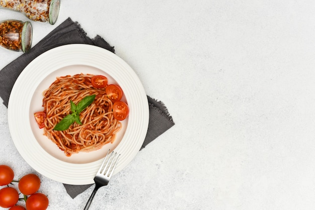 Pasta, spaghetti with tomato sauce and basil in white plate on light background with copy space