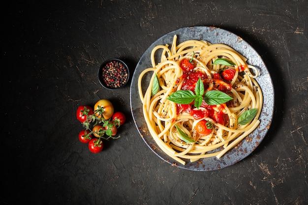 Pasta, spaghetti with tomato sauce in black bowl.