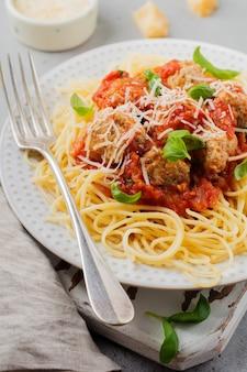 Паста спагетти с томатным соусом, сыром пармезан, базиликом и фрикадельками на белой керамической тарелке на сером фоне бетона или камня