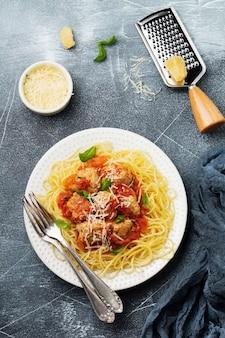 灰色のコンクリート表面の白いセラミックプレートにトマトソース、パルメザンチーズ、バジル、ミートボールのパスタスパゲッティ