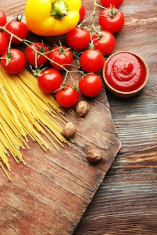 Паста спагетти с помидорами, сыром и базиликом на деревенском деревянном