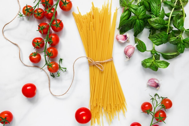 Pasta spaghetti with tomatoes, garlic and basil on white marble background. ingredients for traditional italian dish
