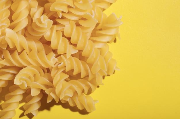 Спираль макаронных изделий сухой сырой фон на ярко-желтом фоне. макаронные изделия из твердых сортов пшеницы. традиционная итальянская еда. еда фон, копия пространства, плоская планировка