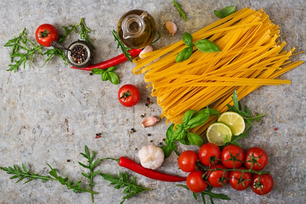 Pasta tagliatelle and ingredients for cooking (tomatoes, garlic, basil, chili). top view