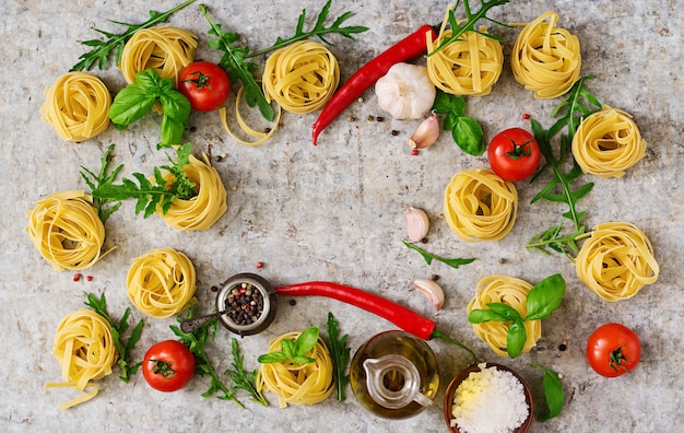 Pasta tagliatelle nest and ingredients for cooking (tomatoes, garlic, basil, chili). top view