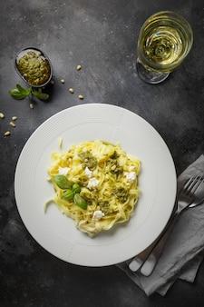 Pasta tagliatelle with pesto, pine nuts, white wine glass on dark. delicious mediterranean lunch.