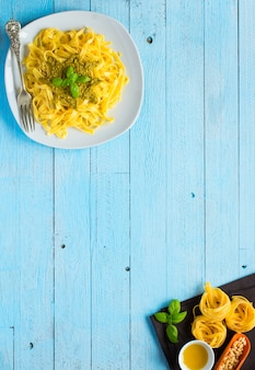 Pasta tagliatelle with pesto sauce and other vegetables on a wood background. top view