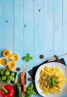 Pasta tagliatelle with pesto sauce and other vegetables on a wood background.