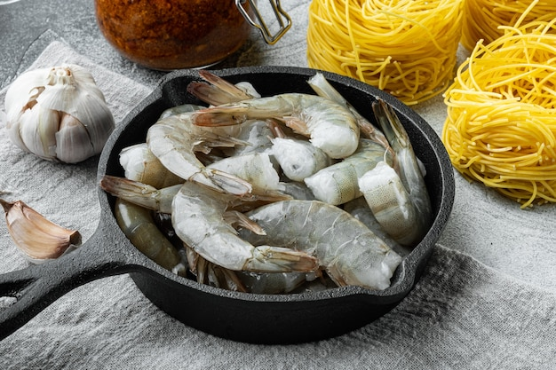 Паста тальерини с соусом песто и креветками на столе из серого камня