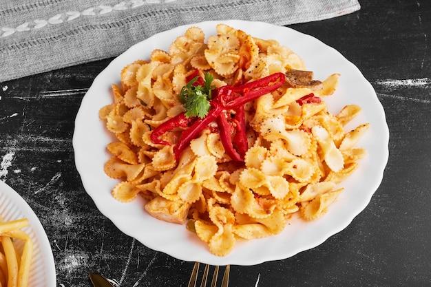 Pasta in salsa di pomodoro in un piatto bianco.