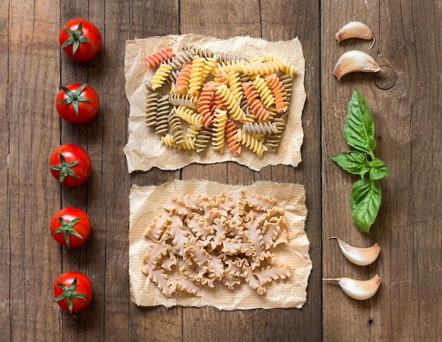 Макароны, помидоры, чеснок и базилик на деревянном фоне вид сверху
