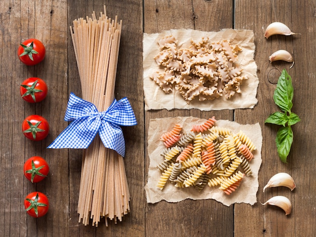 Pasta, tomatoes, garlic and basil on wooden background top view