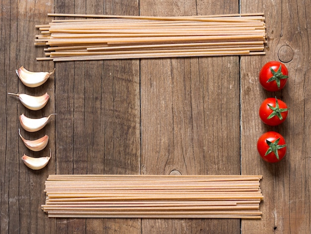 Pasta, tomatoes and garlic frame with copy space on wooden background top view