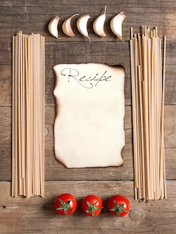 Pasta, tomatoes and garlic frame with paper copy space on wooden background top view