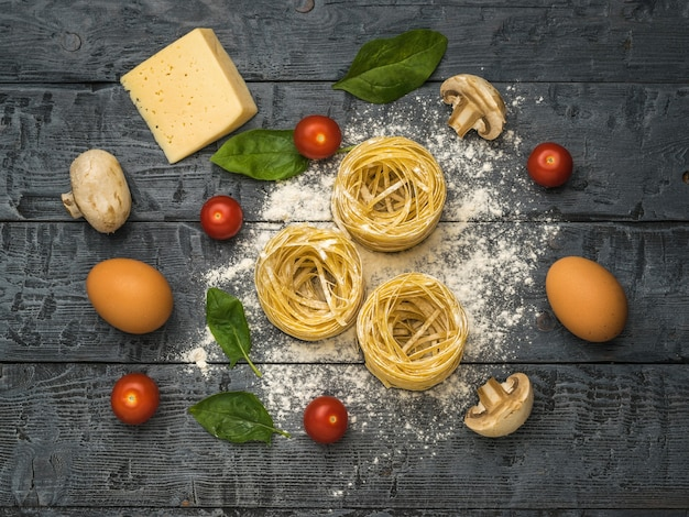Макаронные изделия, помидоры, грибы и яйца на черном деревянном столе. ингредиенты для приготовления макаронных изделий.