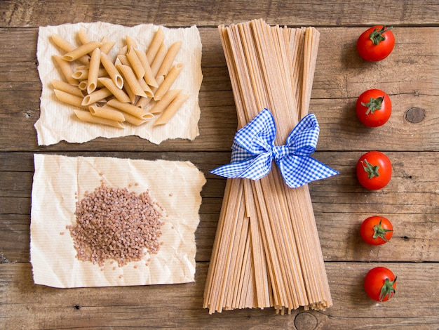 Pasta and  tomatoes on wooden background top view