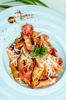 Pasta topped with tomato, cheese and herbs