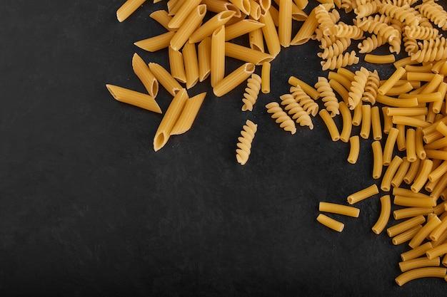 Разновидности макаронных изделий в продуктовом запасе на черном фоне.