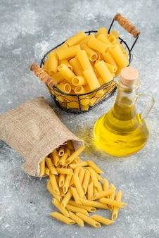 Varietà di pasta in un cesto metallico e una borsa rustica con olio d'oliva sul tavolo grigio.