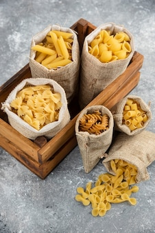Pasta varieties in rustic basket inside a wooden tray.