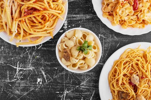 Varietà di pasta in salsa di pomodoro in un piatto bianco su sfondo nero.