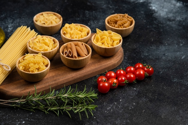 Pasta varieties in wooden cups served with cherry tomatoes and rosemary leaves.