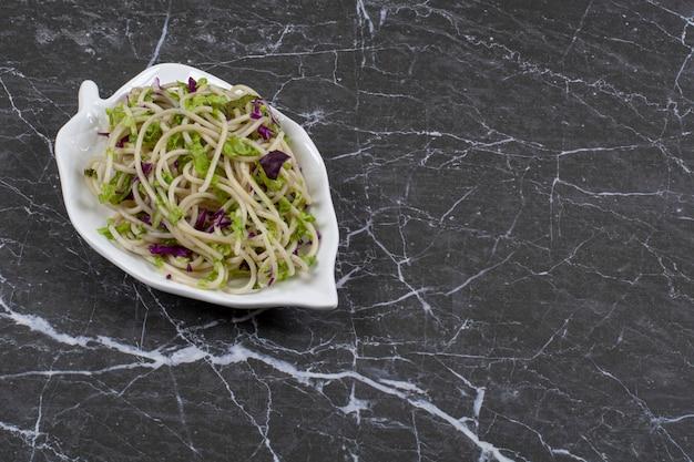 Паста овощной соус на тарелке над черным.