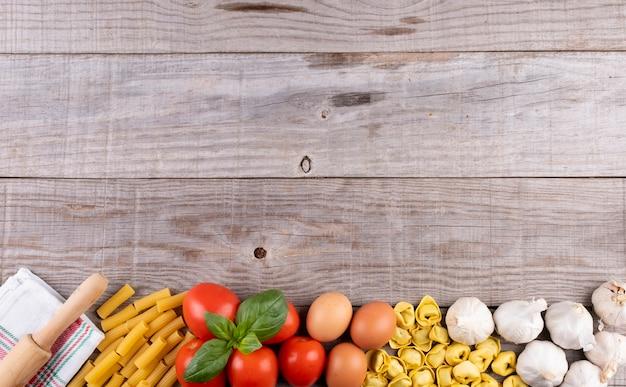 Pasta, vegetables, eggs, on wooden board, ingredients for italian restaurant