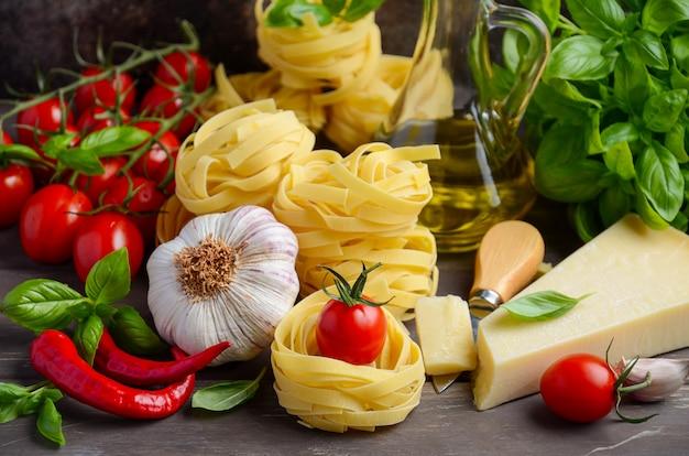 パスタ、野菜、ハーブ、木製の背景にイタリア料理のスパイス。