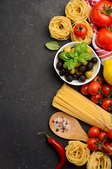 Pasta, vegetables, herbs and spices for italian food on black background