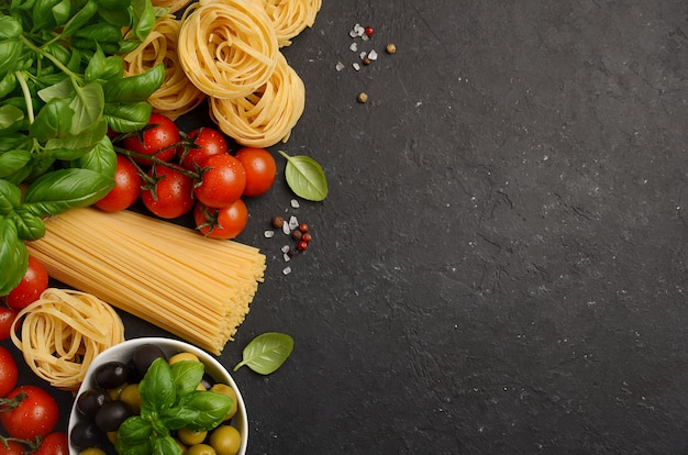 Pasta, vegetables, herbs and spices for italian food on black