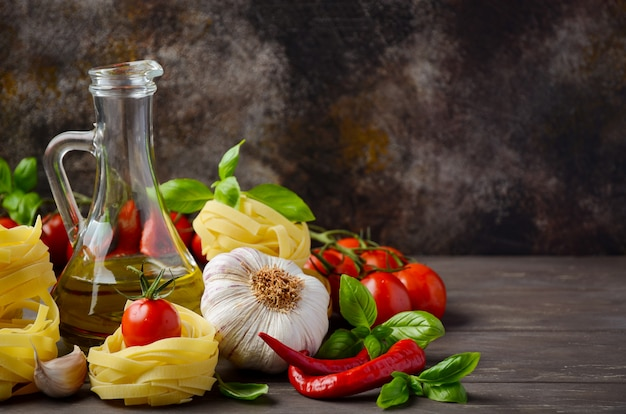Pasta, vegetables, herbs and spices for italian food on the wooden table.