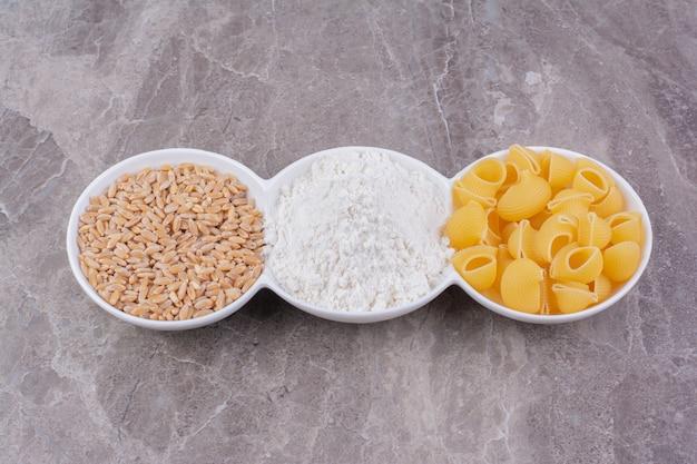 Pasta, grano e farina mista in tripli bicchieri bianchi