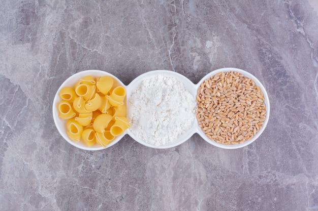 Паста, зерна пшеницы и мука в тройном белом керамическом блюде.