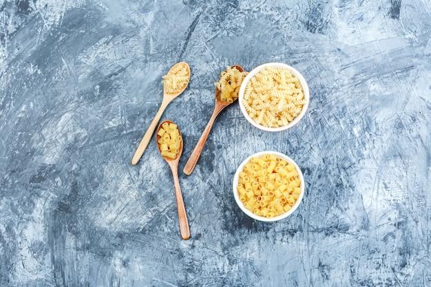 Pasta in ciotole bianche e cucchiai di legno su uno sfondo di gesso grungy. laici piatta.