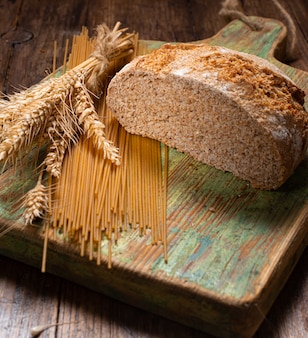 Pasta and wholemeal bread with ears of wheat on the rustic wooden table