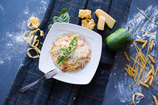 흰 접시에 베이컨, 크림, 바질, 치즈, 마늘, 계란 (노른자위) 파스타