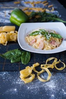 Pasta with bacon, cream, basil, parmesan, garlic, egg (yolk) on white plate.