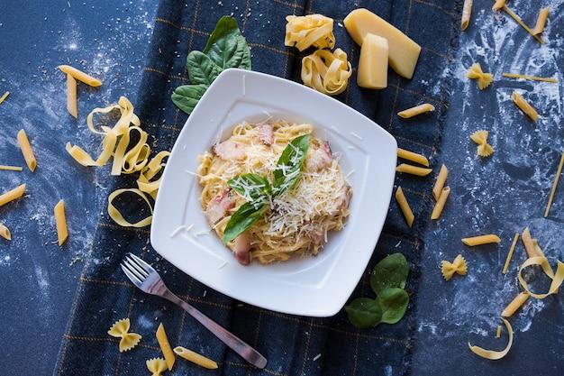 Pasta with bacon, cream, basil, parmesan, garlic, egg (yolk) on white plate