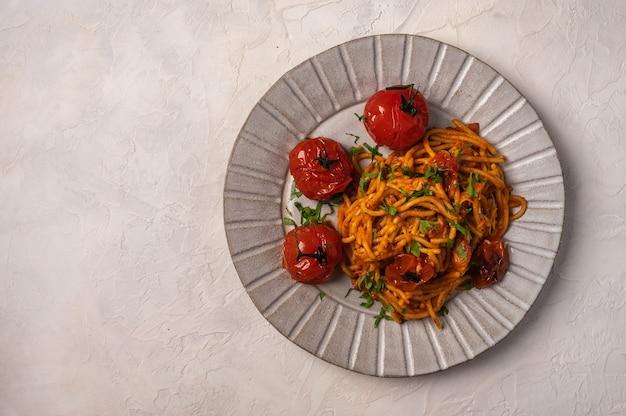 Паста с запеченными помидорами черри, сыром и петрушкой на светлом фоне, вид сверху, копией пространства