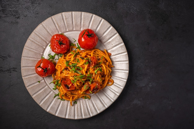 Pasta with baked cherry tomatoes, cheese and parsley on a dark textured background, top view, copy