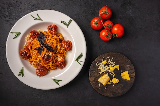 Pasta with baked cherry tomatoes, grated parmesan and pesto sauce on dark graphite background, top view, copy space