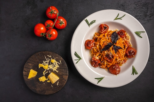 Pasta with baked cherry tomatoes grated parmesan and pesto sauce on dark graphite background top
