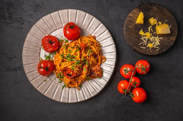 Pasta with baked cherry tomatoes, parmesan and pesto sauce on dark graphite background, top view, copy space